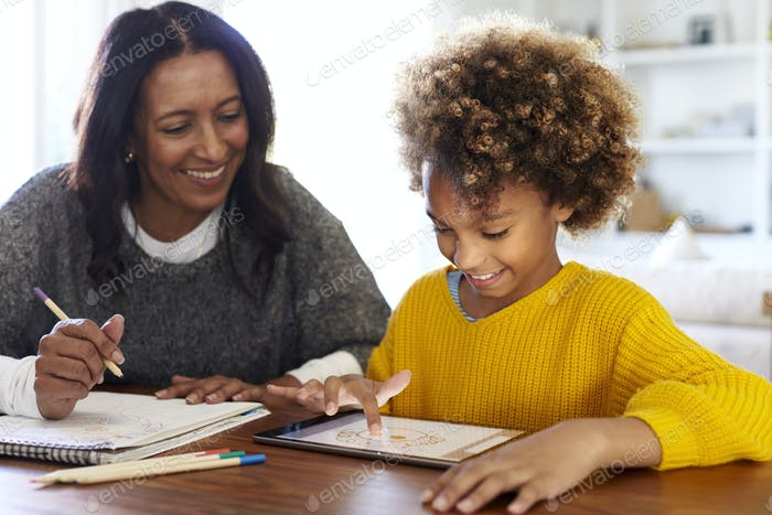 Mixed race young grandmother sitting at table with granddaughter using a tablet computer