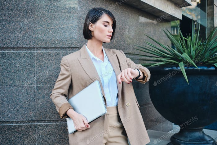Young confident stylish businesswoman in beige suit with laptop watching time on watch outdoor