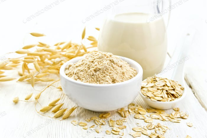 Flour oat in bowl with milk on light wooden board