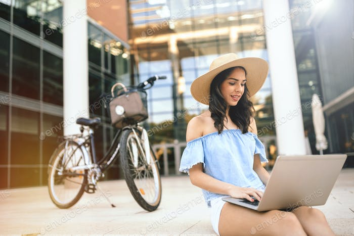 Female student using laptop outdoors