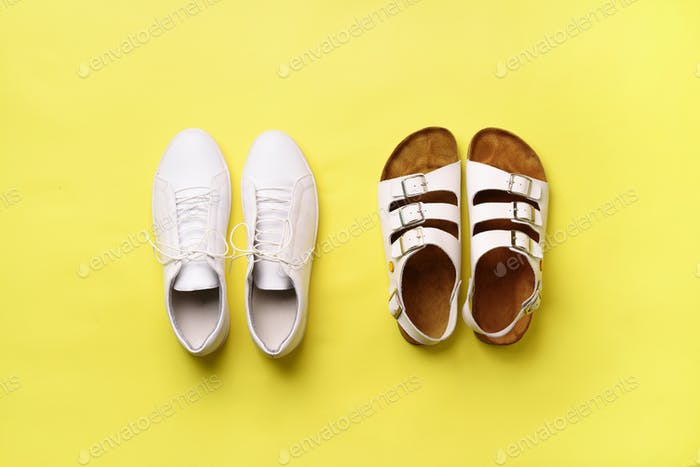 Summer female shoes - sandals birkenstock and leather sneakers on yellow background with copy space