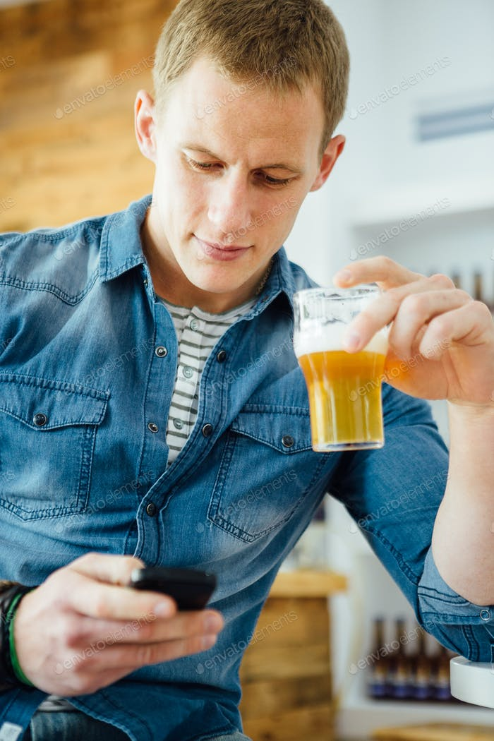 Stylish man with beer using phone