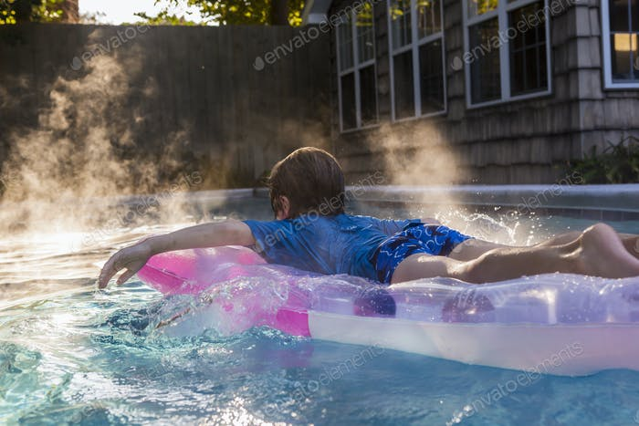 6 year old boy playing in pool at sunrise