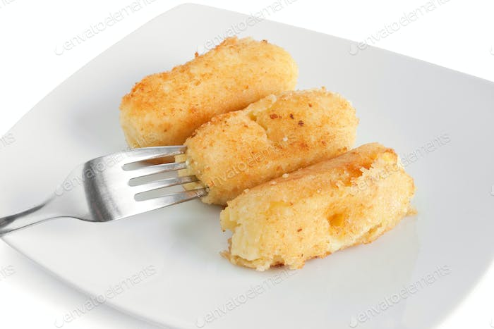 three potato croquettes with fork