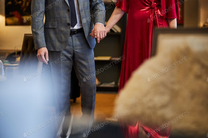 Stylish man and gorgeous woman walking hand in hand