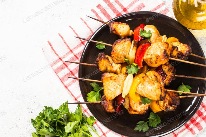 Chicken kebab with vegetables on skewers on white