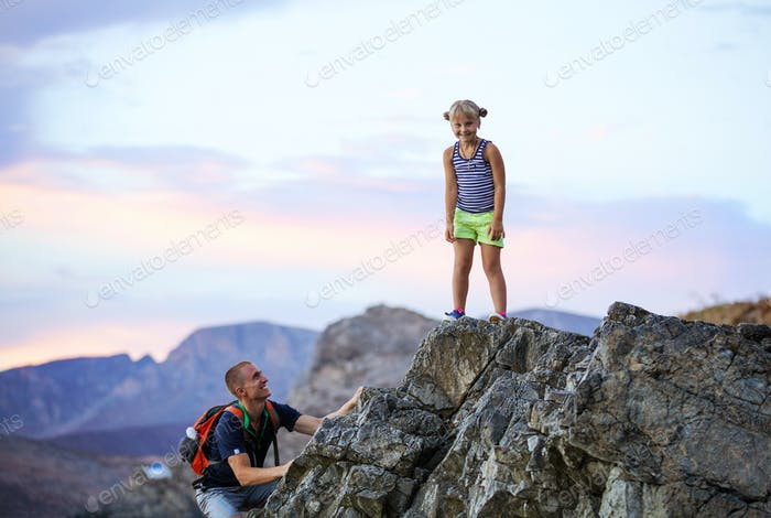 Young girl and father enjoying active vacations in mountains