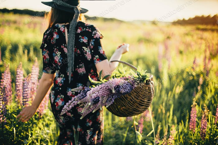 Beautiful woman walking in sunny lupine field, focus on rustic basket with flowers.Tranquil moment