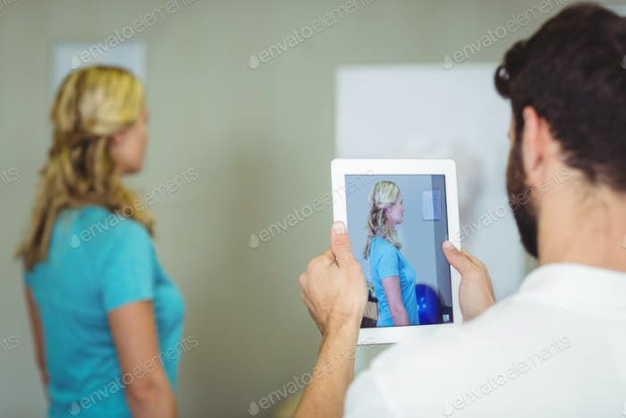 Physiotherapist taking a photograph of a patient with digital table
