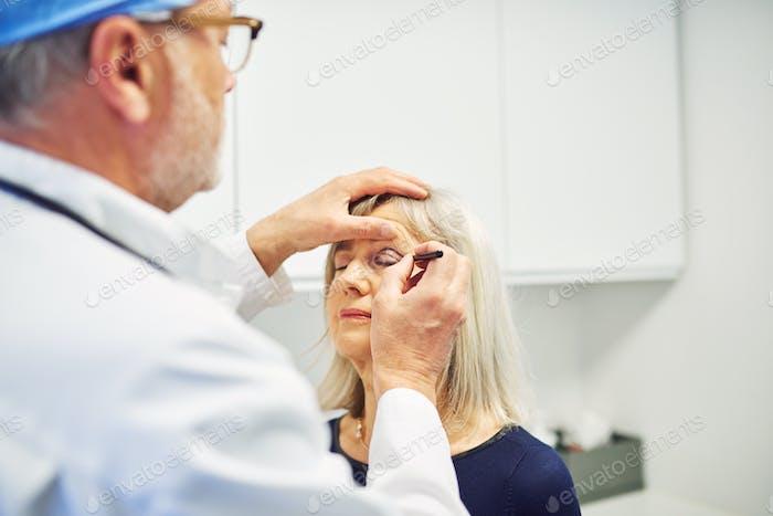 Medic mit Bleistift Planung Gesichtskorrektur für Frau