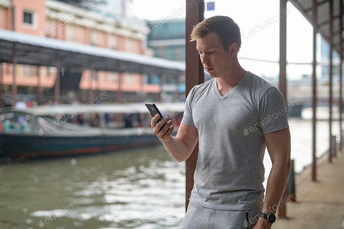 Young handsome tourist man using phone at the local pier in Bangkok