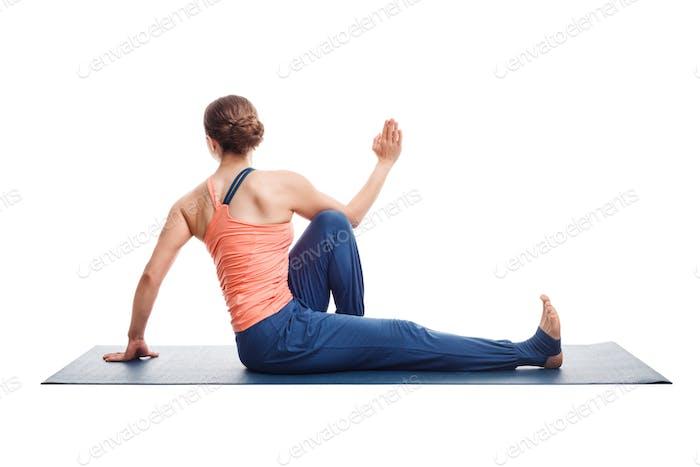 woman practices yoga asana Marichyasana C