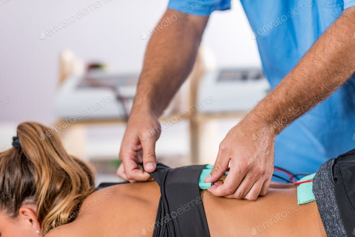 Electrical stimulation in physical therapy. Therapist positionin