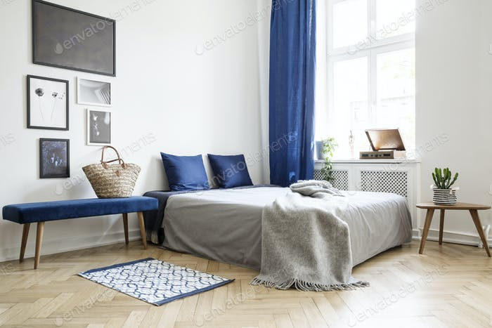 Bedroom design in modern apartment. Bed with dark blue pillows a
