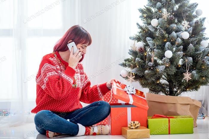 Junge Frau rufen Mobiltelefon von Weihnachtsbaum