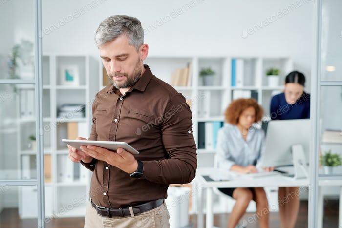 Elegant bearded businessman with touchpad looking at its screen while networking