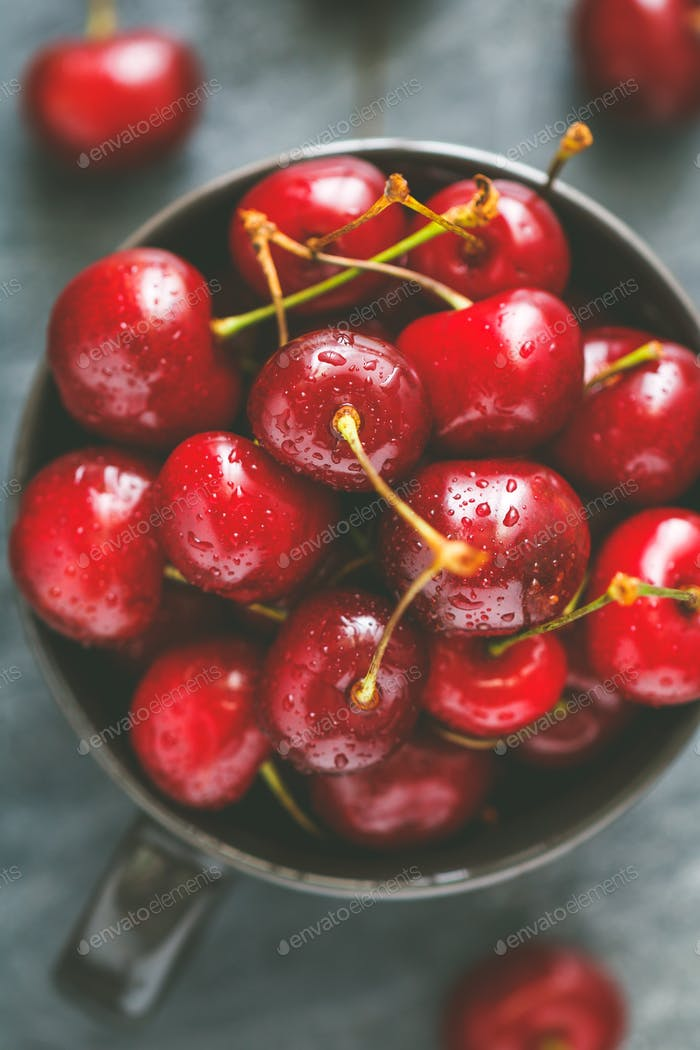 Top view of a bowl with ripe cherry over blue background. The concept of healthy organic food.