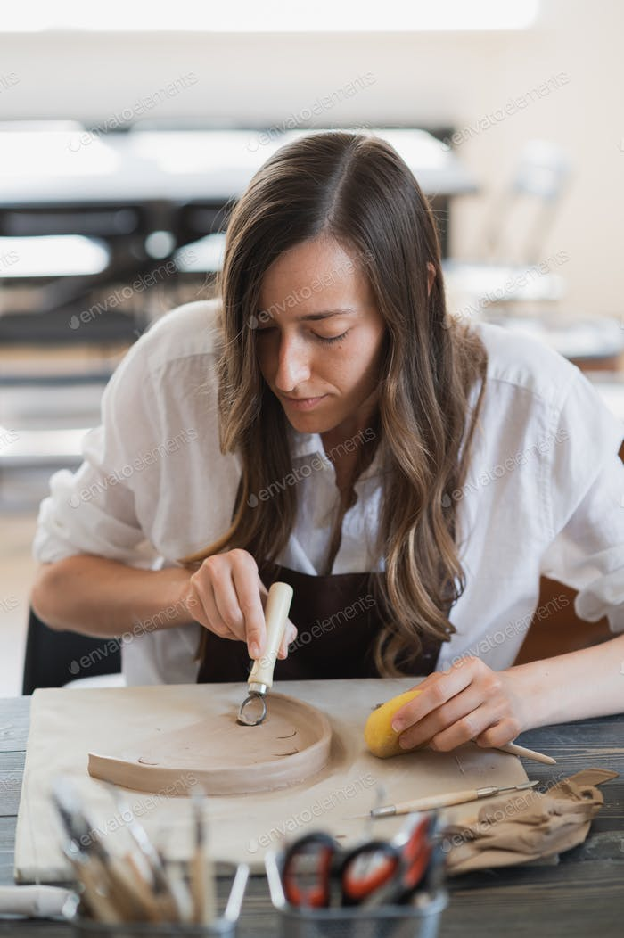 Young woman on a pottery class working with different tools