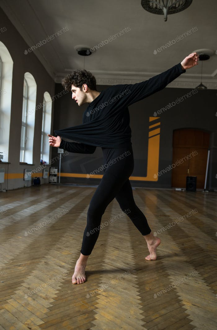 Young man dancing ballet at gym