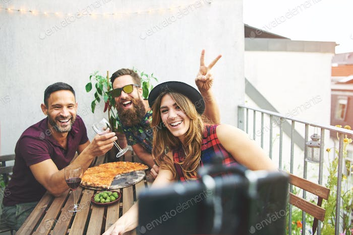 Rabbit ears gesture with friends at table