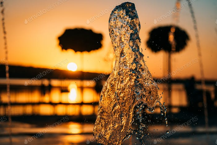stream of a fountain splashes water, sunset