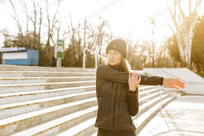 Nahaufnahme Bild von schönen Sportlerin in schwarz Trainingsanzug Warmin