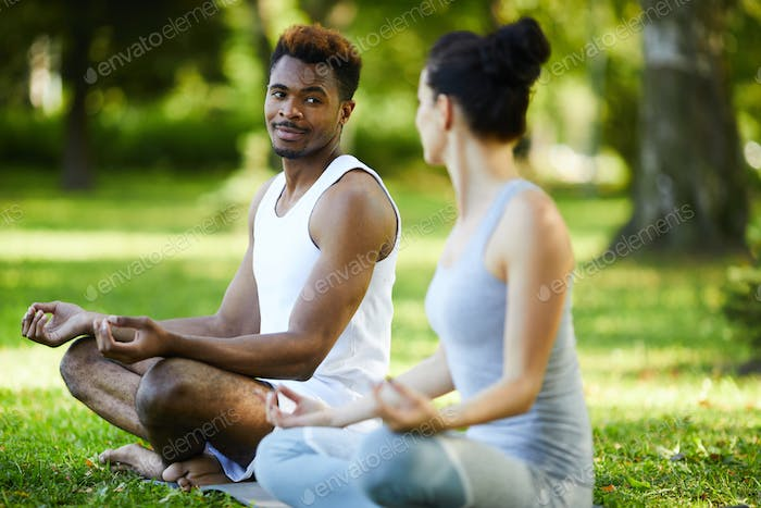 Content interracial couple talking during outdoor yoga practice