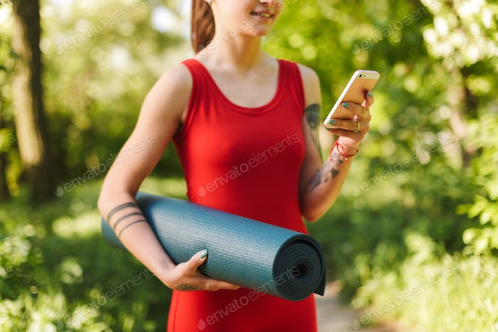 Young woman in red jumpsuit standing with yoga mat in hand and using cellphone