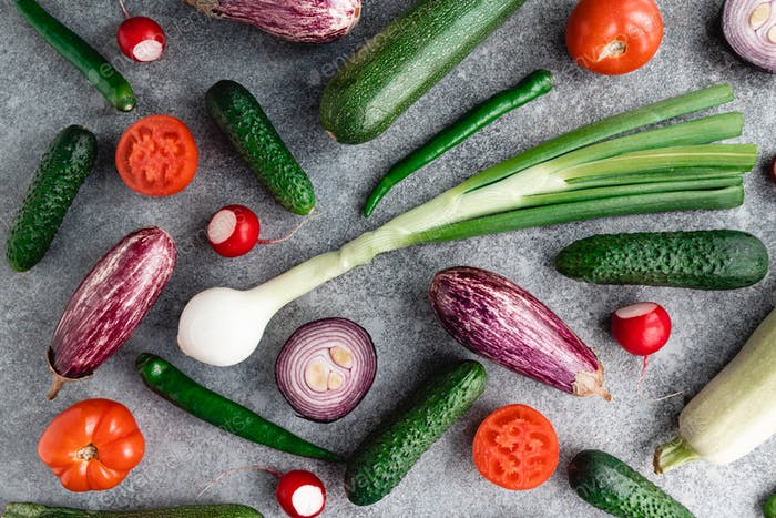 Colorful summer pattern with different fresh vegetables on a grey background.