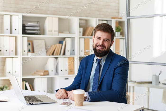 Lächelnder Geschäftsmann am Schreibtisch im Büro