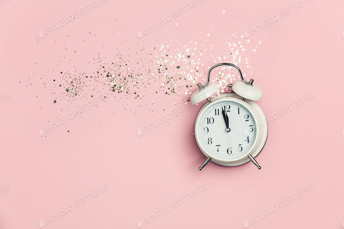 Creative composition with alarm clock and golden stars confetti on pink background