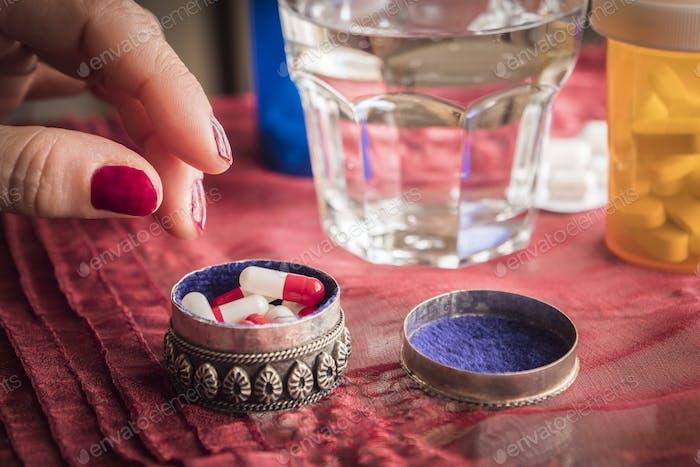 Hand Frauen nehmen Kapseln rot und weiß in einer Pillenbox Metalic alt