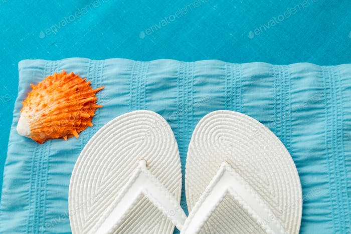White flip flop near seashell
