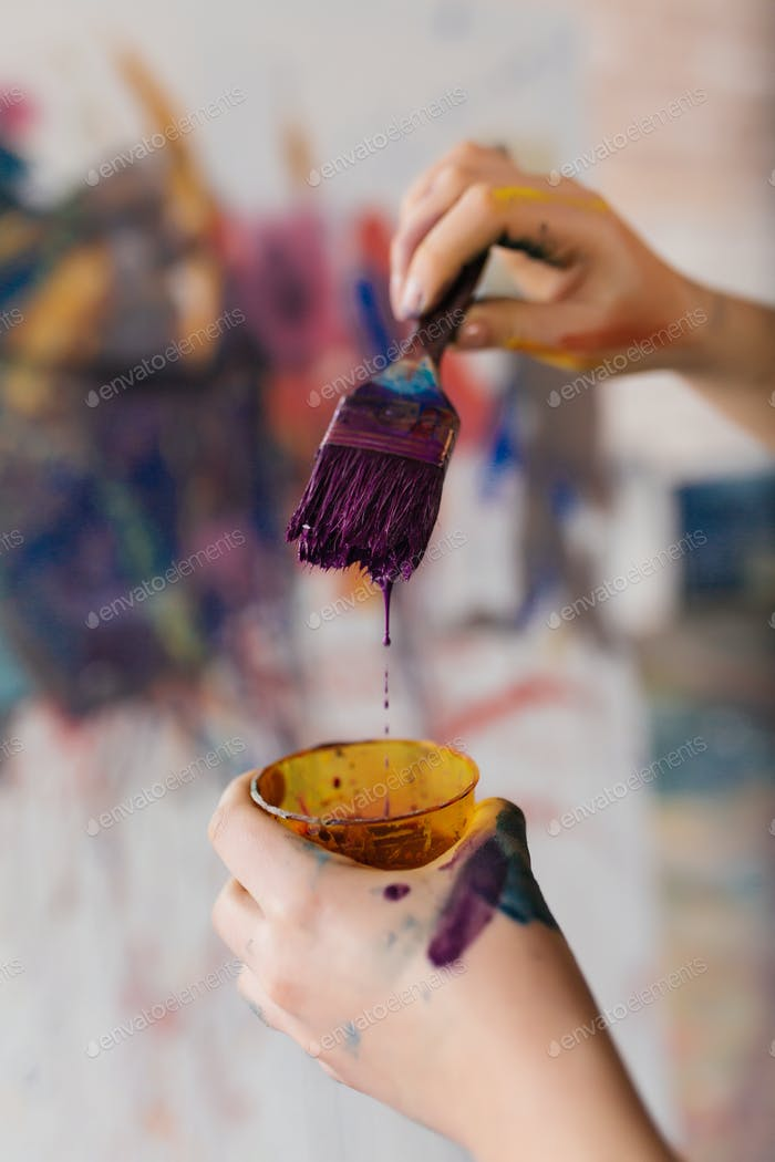 Close up photo of woman hands in paints holding paintbrush prepa