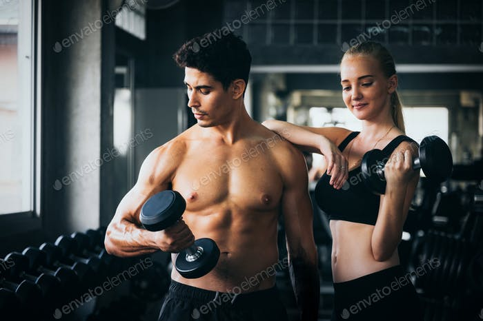 people with Dumbbells in sport gym