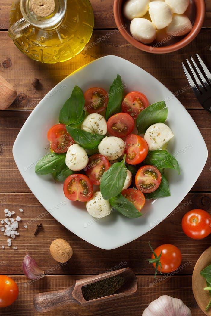caprese salad and ingredients at wood