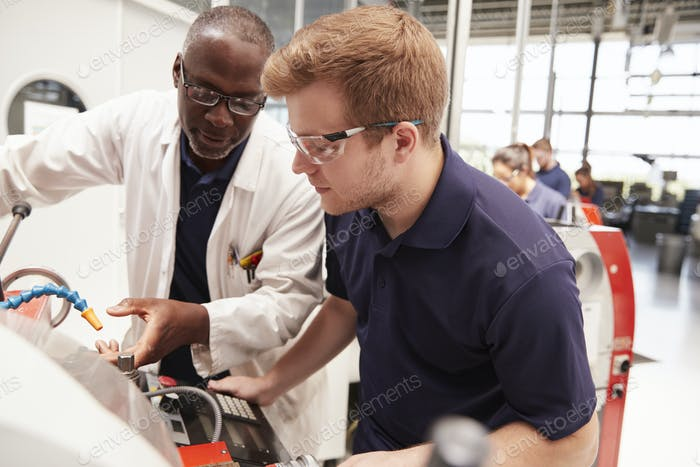 Engineer giving guidance to apprentice in factory, close up