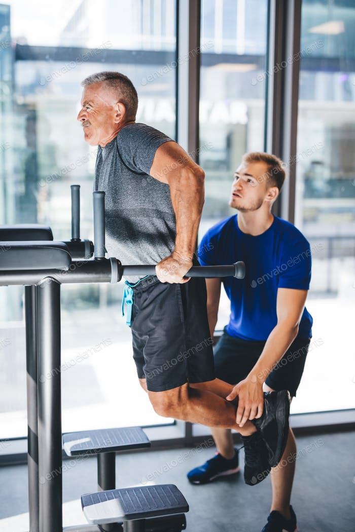 Man helping senior man with his workout at a gym.