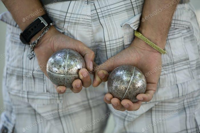 Ein Boulespieler mit einer Metallkugel in jeder Hand, der hinter seinem Rücken gehalten wird.