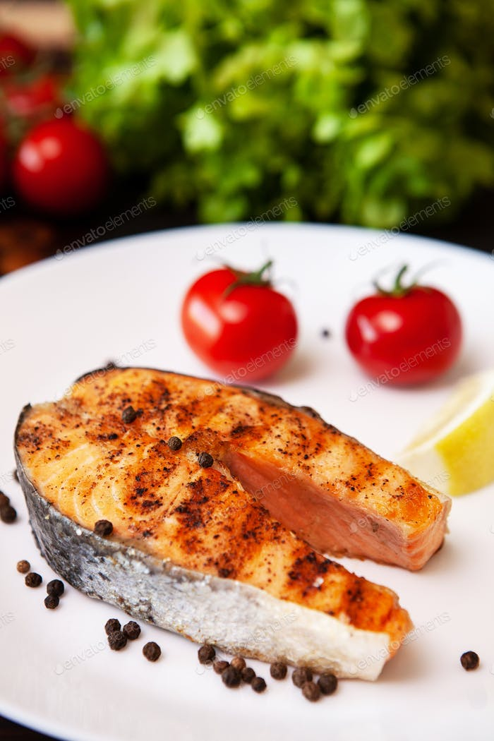 Salmon cooked on the grill arranged on a plate with tomatoes and black pepper