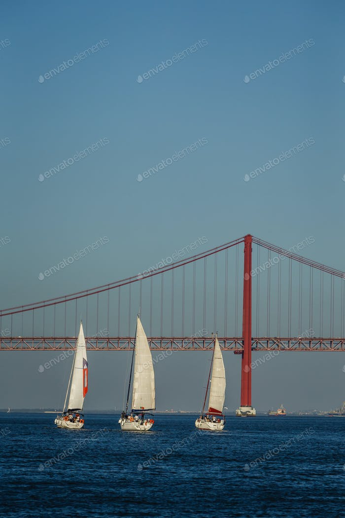 Boats sailing in river Tagus with bridge in Lisbon, Portugal