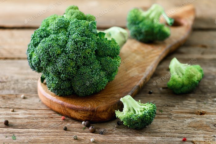 Fresh organic broccoli on wooden table close up with copyspace