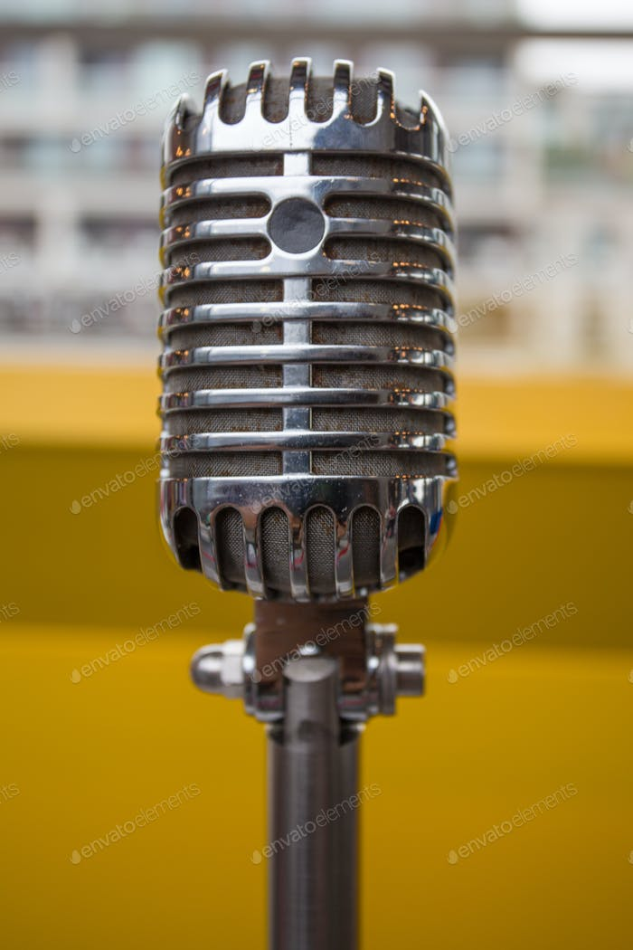 Vintage microphone on a yellow background