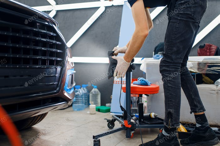 Male worker dries car protection film, auto tuning