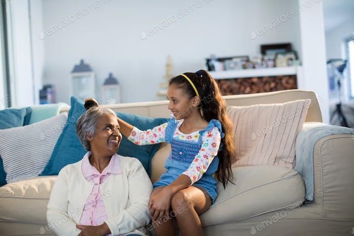 Granddaughter brushing her grandmothers hair in living room