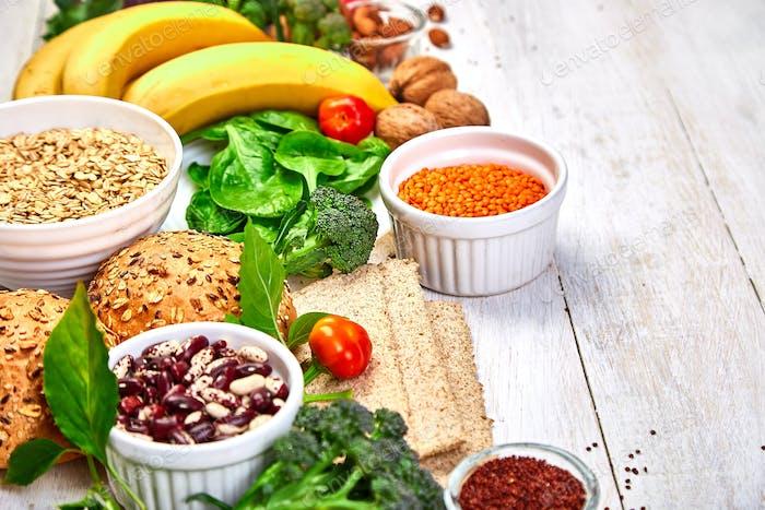Auswahl Lebensmittel reich an Ballaststoffen auf weißem Holzhintergrund.