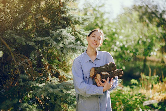 Girl in a blue shirt standing on trees background