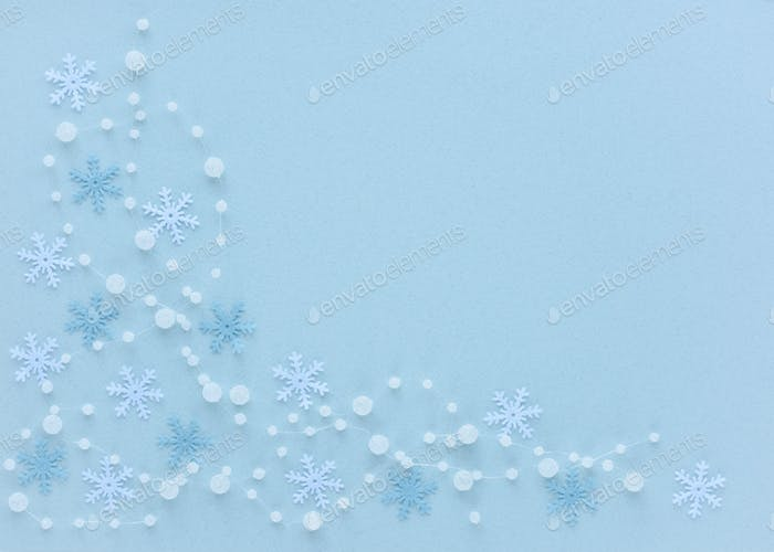 Snowflakes and beads on pastel blue background
