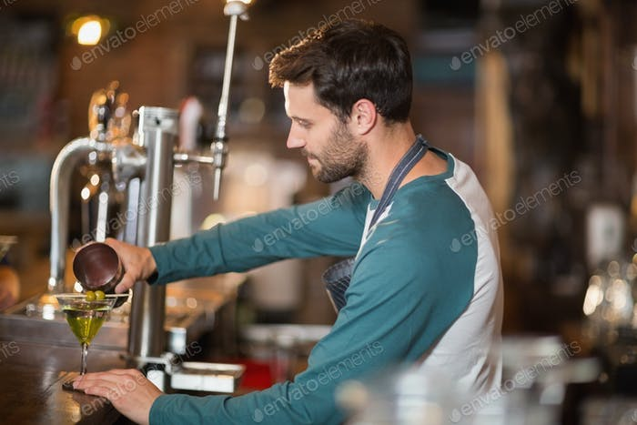 Side view of bartender making drinks