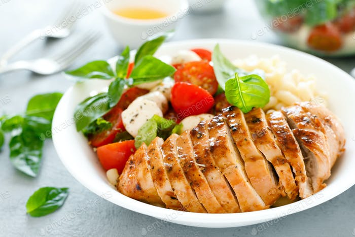 Grilled chicken lunch bowl with orange juice dressing, pasta and caprese salad